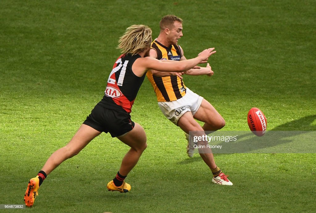 Tom Mitchell of the Hawks kicks whilst being tackled by Dyson Heppell of the Bombers during the round seven AFL match between the Essendon Bombers and the Hawthorn Hawks at Melbourne Cricket Ground on May 5, 2018 in Melbourne, Australia.