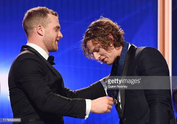 Tom Mitchell of the Hawks presents Nat Fyfe of the Dockers the 2019 Brownlow Medal during the 2019 Brownlow Medal at Crown Palladium on September 23...