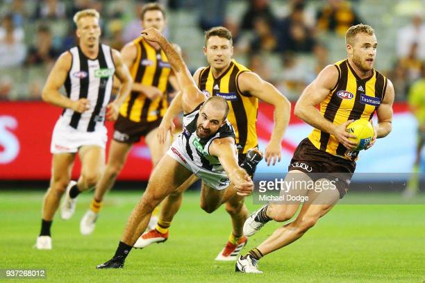 Tom Mitchell of the Hawks runs with the ball from Steele Sidebottom of the Magpies during the round one AFL match between the Hawthorn Hawks and the...