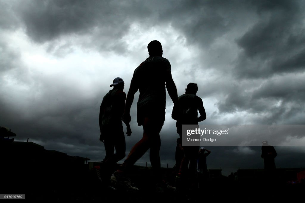 Tom Mitchell of the Hawks (C) walks out as a storm whips through in the background during a Hawthorn Hawks AFL training session on February 14, 2018 in Melbourne, Australia.