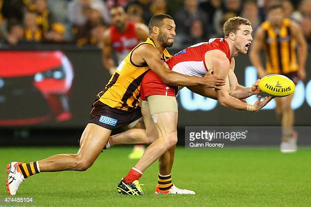 Tom Mitchell of the Swans handballs whilst being tackled by Josh Gibson of the Hawks during the round eight AFL match between the Hawthorn Hawks and...