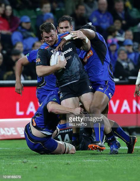 Tom Moloney of Japan's Wild Knights attempts to break through a tackle from Harrison Orr and Feleti Kaiutu by from Western Force during their World...