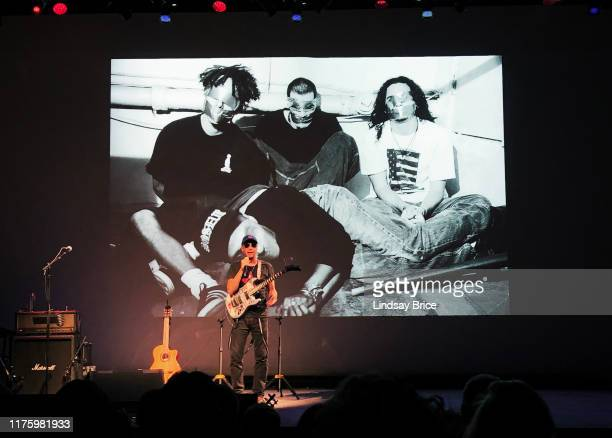 Tom Morello performs SPEAKING TRUTH TO POWER THROUGH STORIES AND SONG before projection of 1992 photograph of Rage Against the Machine by this...
