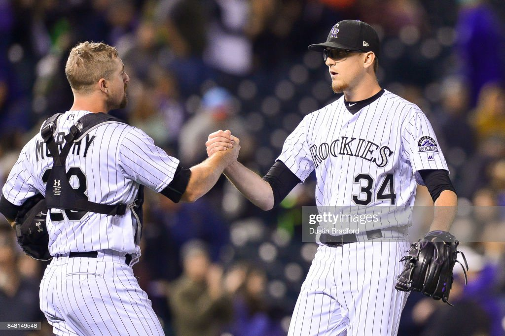 Tom Murphy #23 and Jeff Hoffman #34 of the Colorado Rockies celebrate the end of a 16-0 win over the San Diego Padres at Coors Field on September 16, 2017 in Denver, Colorado.