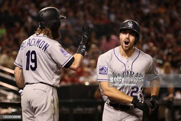 Tom Murphy of the Colorado Rockies high fives Charlie Blackmon after hitting a solo home run against the Arizona Diamondbacks during the eighth...