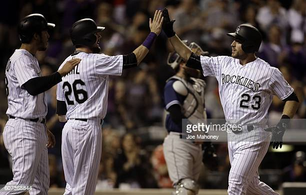 Tom Murphy of the Colorado Rockies high fives David Dahl of the Colorado Rockies and Nolan Arenado of the Colorado Rockies after Murphy's threerun...