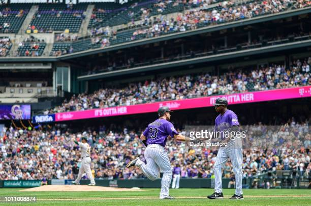 Tom Murphy of the Colorado Rockies is congratulated by third base coach Stu Cole as he rounds the bases after hitting a second inning two run homerun...
