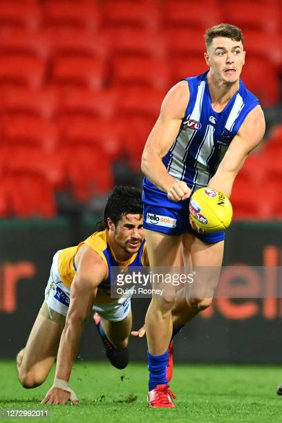 Tom Murphy of the Kangaroos handballs whilst being tackled during the round 18 AFL match between the North Melbourne Kangaroos and the West Coast...
