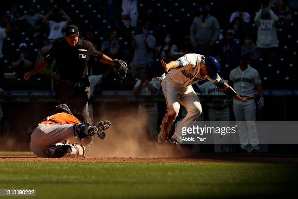 Tom Murphy of the Seattle Mariners beats the tag by Jason Castro of the Houston Astros to score off an RBI double by Mitch Haniger during the seventh...