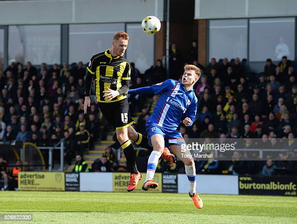 Tom Naylor of Burton Albion is challenged by Jake Hessenthaler of Gillingham during the Sky Bet League One match between Burton Albion and Gillingham...