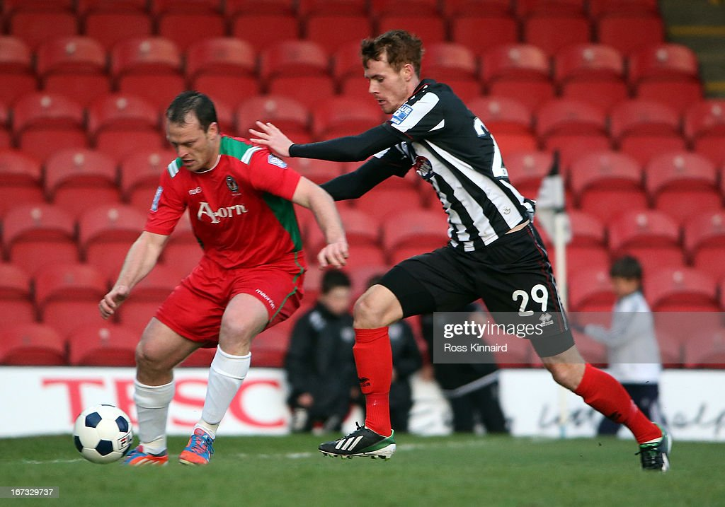 Tom Naylor of Grimsby is challenged by Michael Flynn of Newport during the Blue Square Bet Premier Conference Play-off: First Leg match between Grimsby Town and Newport County at Blundell Park on April 24, 2013 in Grimsby, England.