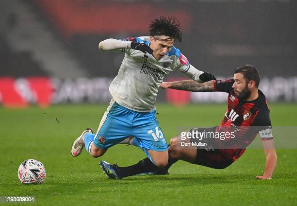 Tom Nichols of Crawley Town is challenged by Steve Cook of AFC Bournemouth during The Emirates FA Cup Fourth Round match between AFC Bournemouth and...