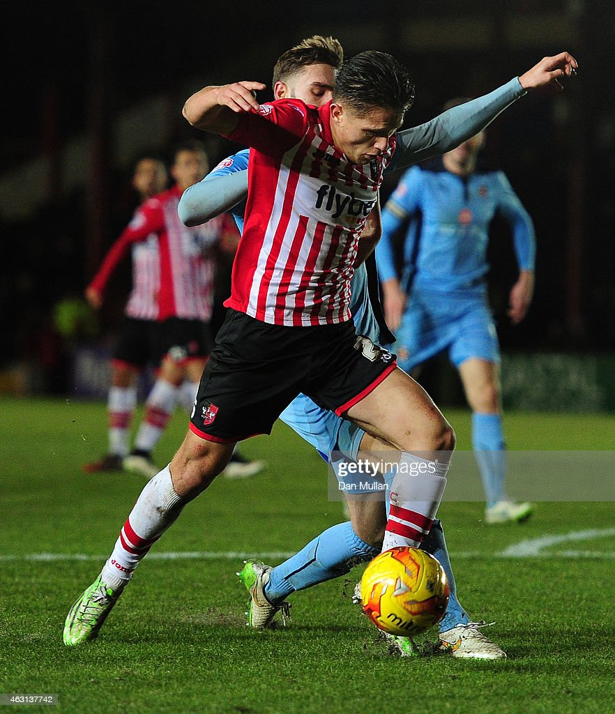 Tom Nichols of Exeter City holds off Greg Taylor of Cambridge United during the Sky Bet League Two match between Exeter City and Cambridge United at St. James Park on February 10, 2015 in Exeter, England.