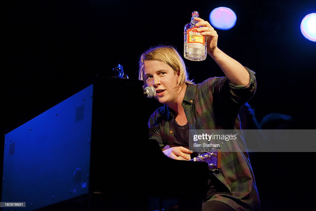 Tom Odell offers the crowd a drink as he performs on stage in concert at Cockpit on March 2, 2013 in Leeds, England.