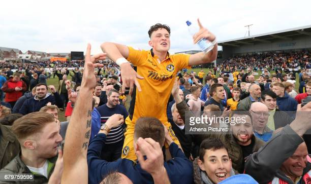 Tom OwenEvans of Newport County is surrounded by fans as a pitch invasion occurs after the final whistle of the Sky Bet League Two match between...