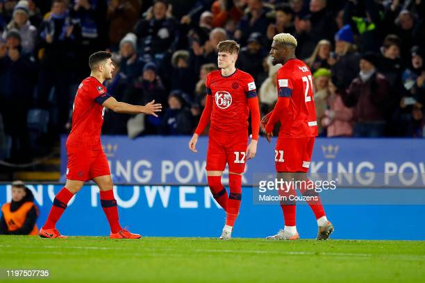 Tom Pearce of Wigan Athletic is consoled by Sam Morsy and Cedric Kipre following his own goal during the FA Cup Third Round match between Leicester...