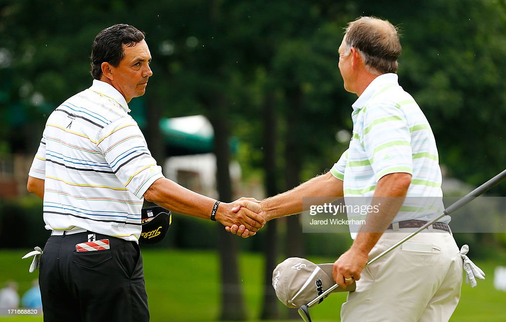 Tom Pernice Jr. shakes hands with Mike Goodes on the green of the 18th hole during the first round of the 2013 Constellation Senior Players Championship at Fox Chapel Golf Club on June 27, 2012 in Fox Chapel, Pennsylvania.