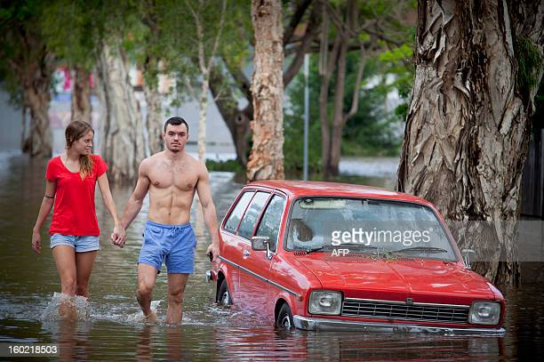 Tom Pfeffer and his girlfriend Greta Devlin walk past a partly submerged car in the flooded inner Brisbane suburb of Newmarket on January 28 2013 as...