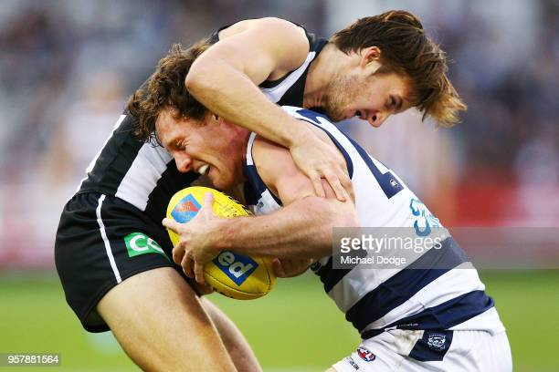 Tom Phillips of the Magpies tackles Jed Bews of the Cats during the round eight AFL match between the Collingwood Magpies and the Geelong Cats at...