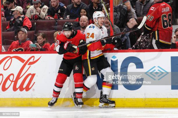 Tom Pyatt of the Ottawa Senators checks Travis Hamonic of the Calgary Flames along the boards in the second period at Canadian Tire Centre on March 9...