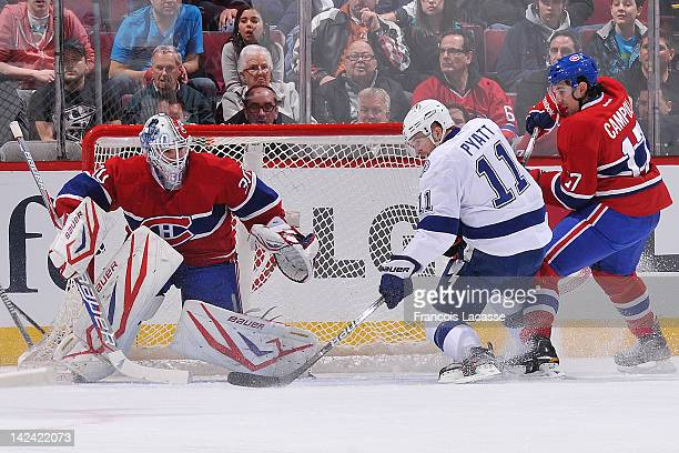 Tom Pyatt of the Tampa Bay Lightning is defended by Chris Campoli of the Montreal Canadiens as he tries to find a loose puck in front of goalie Peter...