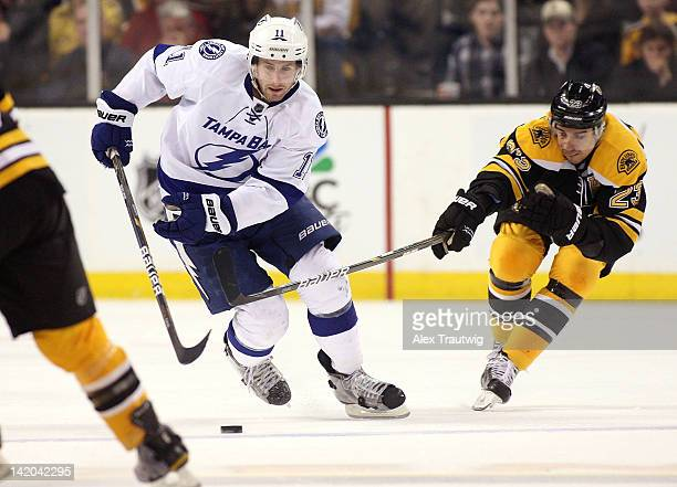 Tom Pyatt of the Tampa Bay Lightning protects the puck from Chris Kelly of the Boston Bruins at TD Garden on March 27 2012 in Boston Massachusetts