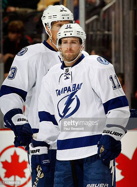 Tom Pyatt of the Tampa Bay Lightning talks with teammate Keith Aulie during an NHL hockey game against the New Jersey Devils at Prudential Center on...