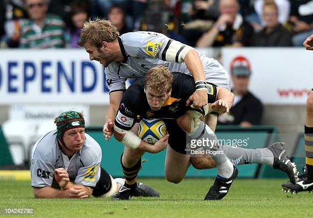 Tom Rees of Wasps is tackled by Tom Croft as Thomas Waldrom looks on during the Aviva Premiership match between London Wasps and Leicester Tigers at...