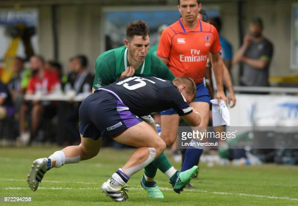 Tom Roche of Ireland is tackled during the World Rugby U20 Championship semi final match between Ireland and Scotland at Stade AimeGiral on June 12...