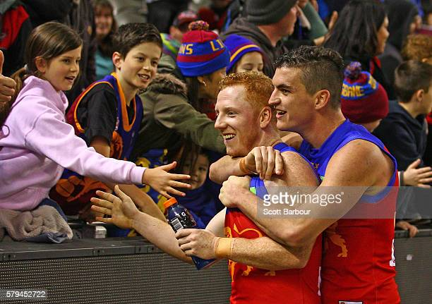 Tom Rockliff and Josh Green of the Lions embrace as they thank supporters in the crowd after the Lions won the round 18 AFL match between the...