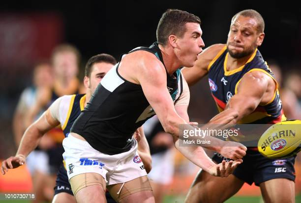 Tom Rockliff of Port Adelaide handballs under pressure from Cam EllisYoleman of the Adelaide Crows during the round 20 AFL match between the Adelaide...