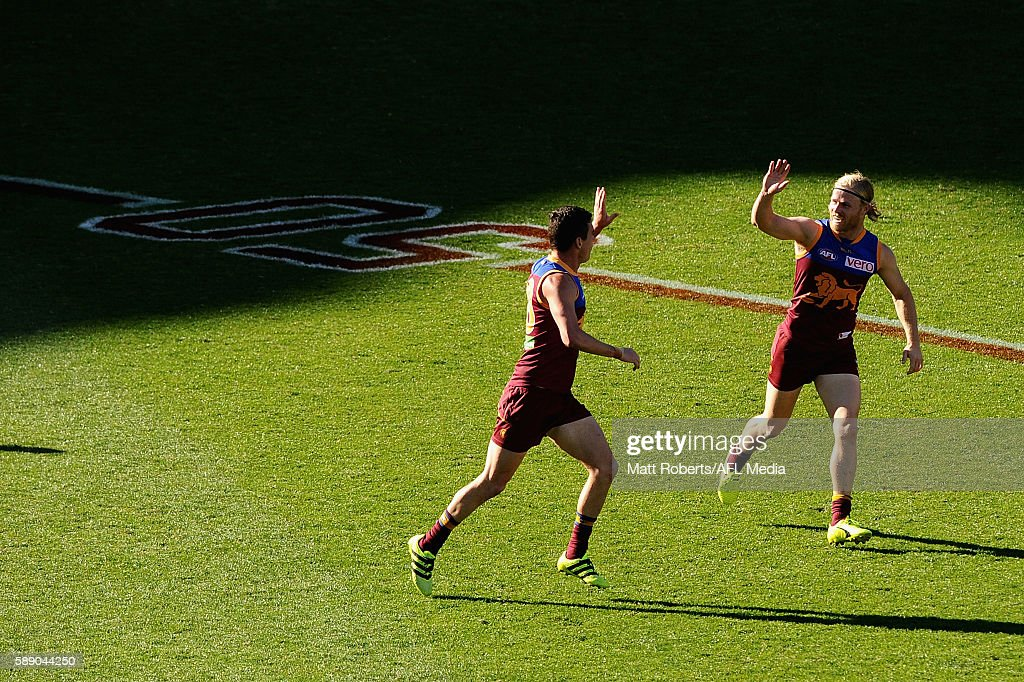 Tom Rockliff of the Lions celebrates kicking a goal with Daniel Rich during the round 21 AFL match between the Brisbane Lions and the Carlton Blues at The Gabba on August 13, 2016 in Brisbane, Australia.