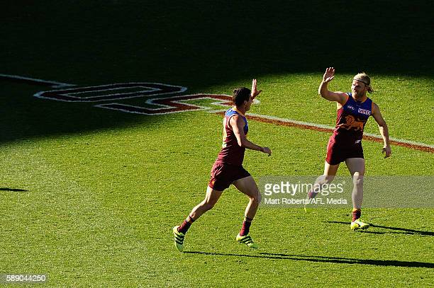Tom Rockliff of the Lions celebrates kicking a goal with Daniel Rich during the round 21 AFL match between the Brisbane Lions and the Carlton Blues...