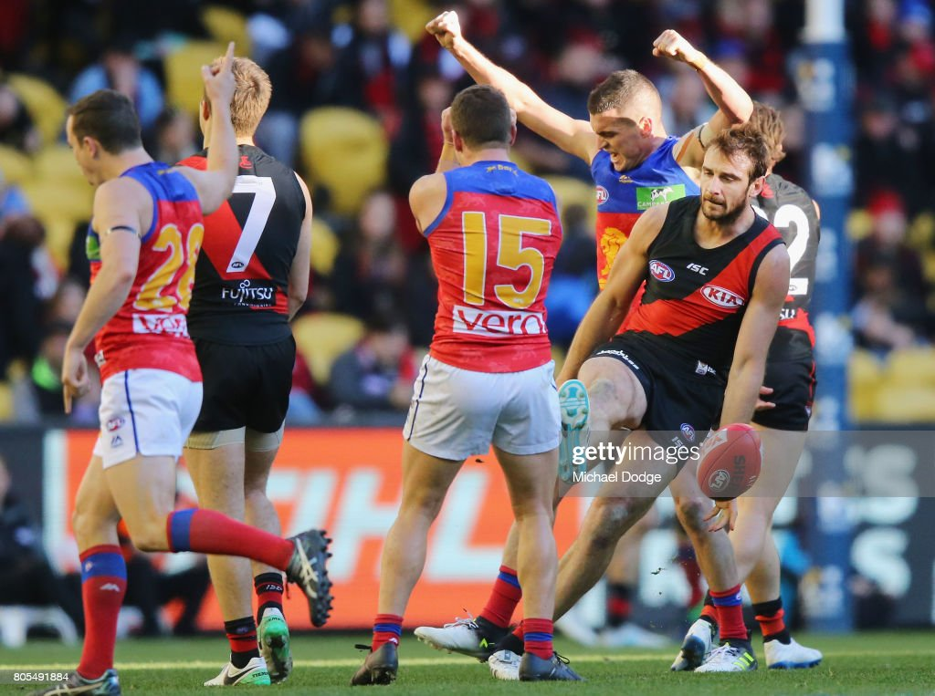Tom Rockliff of the Lions celebrates with Dayne Zorko and Lewis Taylor (L) after their win on the final siren as Jobe Watson of the Bombers kicks the ball away in dejection during the round 15 AFL match between the Essendon Bombers and the Brisbane Lions at Etihad Stadium on July 2, 2017 in Melbourne, Australia.