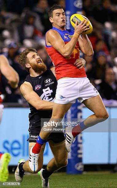 Tom Rockliff of the Lions marks infront of Zach Tuohy of the Blues during the round six AFL match between the Carlton Blues and the Brisbane Lions at...