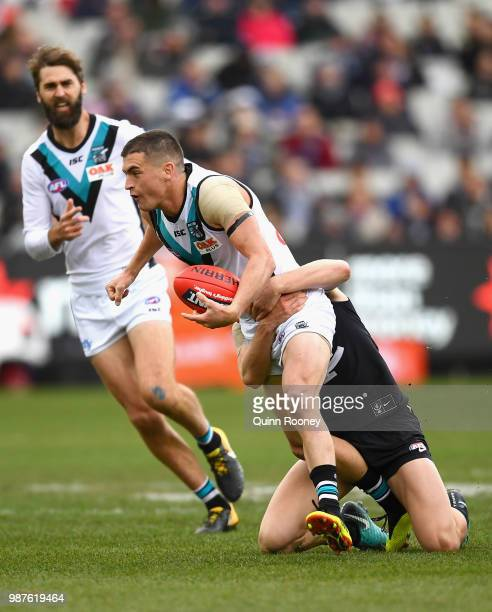 Tom Rockliff of the Power is tackled by Paddy Dow of the Blues during the round 15 AFL match between the Carlton Blues and the Port Adelaide Power at...