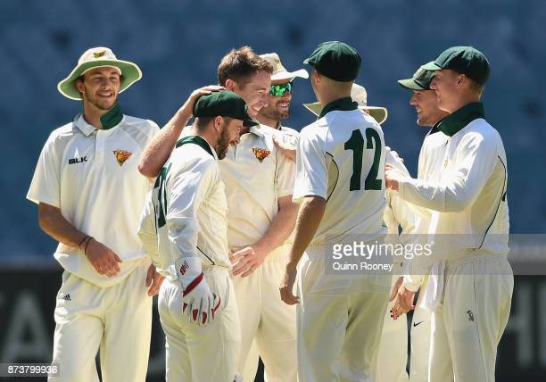 Tom Rogers of Tasmania is congratulated by team mates after taking the wicket of Marcus Harris of Victoria during day two of the Sheffield Shield...