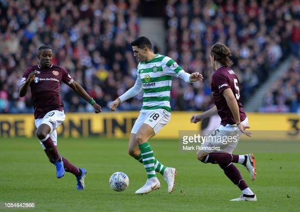 Tom Rogic of Celtic is challenged by Peter Haring and Arnaud Djoum of Hearts during the Betfred Scottish League Cup Semi Final between Heart of...