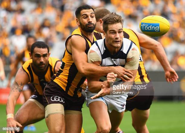 Tom Ruggles of the Cats handballs whilst being tackled by Paul Puopolo of the Hawks during the round four AFL match between the Hawthorn Hawks and...