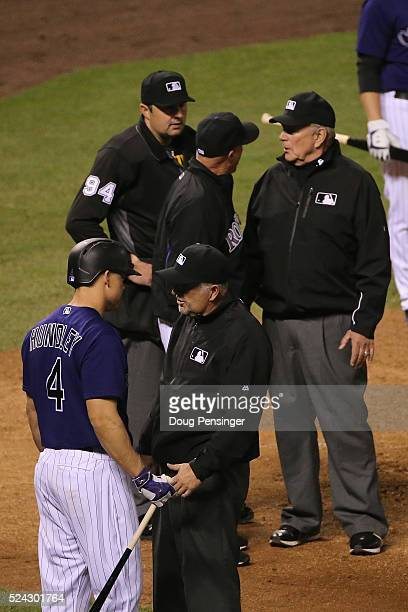 Tom Runnells of the Colorado Rockies argues with umpire Lance Barrett and umpire Bob Davidson as Nick Hundley of the Colorado Rockies converses with...