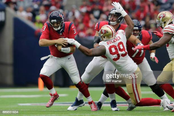 Tom Savage of the Houston Texans avoids a tackle by DeForest Buckner of the San Francisco 49ers in the first quarter at NRG Stadium on December 10...