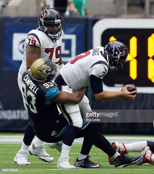 Tom Savage of the Houston Texans is sacked by Calais Campbell of the Jacksonville Jaguars as Jeff Allen looks on at NRG Stadium on September 10 2017...