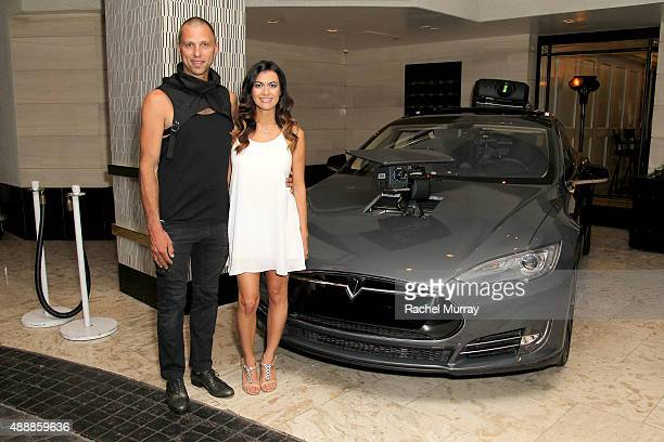 Tom Sepe and Race car driver Leilani Munter pose with a Tesla Model S during the Los Angeles premiere of RACING EXTINCTION at The London West...