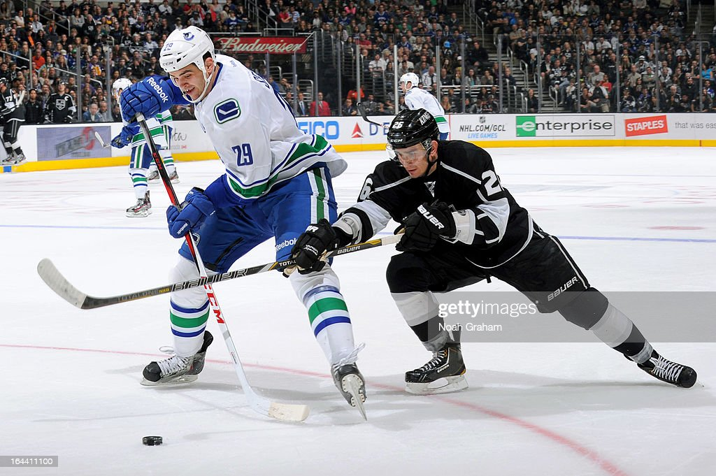 Tom Sestito #29 of the Vancouver Canucks battles for the puck against Slava Voynov #26 of the Los Angeles Kings at Staples Center on March 23, 2013 in Los Angeles, California.