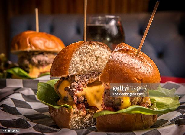 Tom Sietsema's First Bite on Slash Run on August 2015 in Washington DC Pictured a Juicy Lucy burger cut in half to show the cheese melting from the...