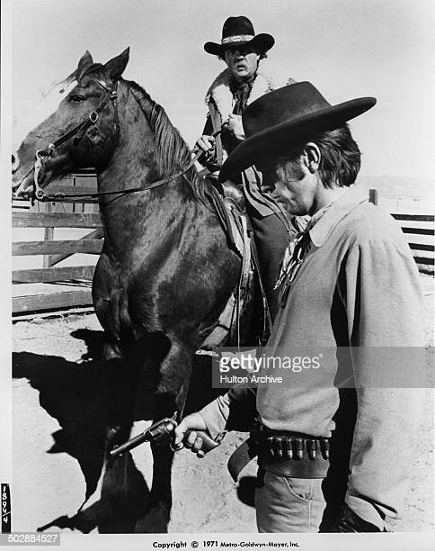 Tom Skerritt looks forlorn as Karl Malden rides up in a scene for the the MGM movie 'Wild Rovers' circa 1971