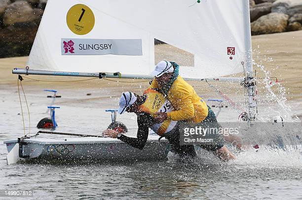 Tom Slingsby of Australia is pulled into the water by team mate Brendan Casey after winning gold in the Men's Laser Sailing on Day 10 of the London...