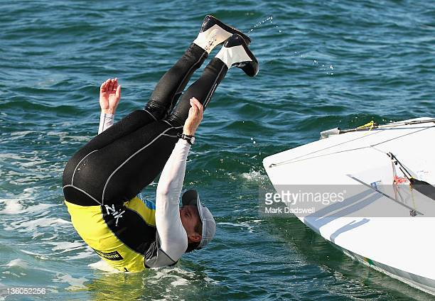 Tom Slingsby of Australia somersaults into the water as he celebrates winning the Laser Men's One Person Dinghy Medal race on the Centre Course...