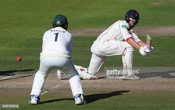Tom Smith of Lancashire sweeps the ball for four runs during the Specsavers County Championship division one match between Nottinghamshire and...