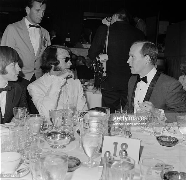 Tom Smothers talks with Michael Nesmith and Peter Tork of The Monkees the Emmy Awards in Los AngelesCA
